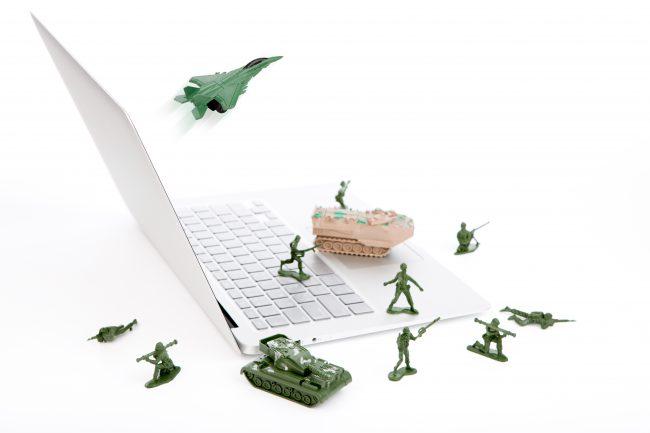 Toy army men on laptop - long-term impact of cyber crime.