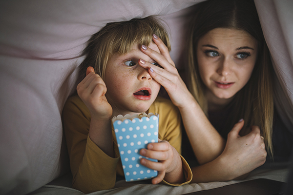 Scared kids watching a scary movie so they're scared.