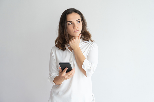 Young woman holding phone and pondering something.