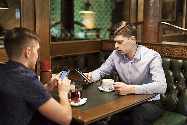 Two young men with identical haircuts, in a pub or coffee shop, ignoring each other and using their phones instead of talking to each other - Wetherspoons