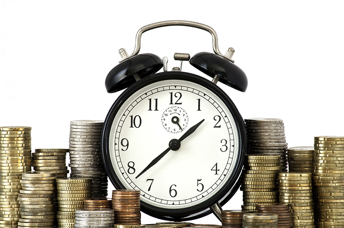 Clock surrounded by coins. Early adopter.
