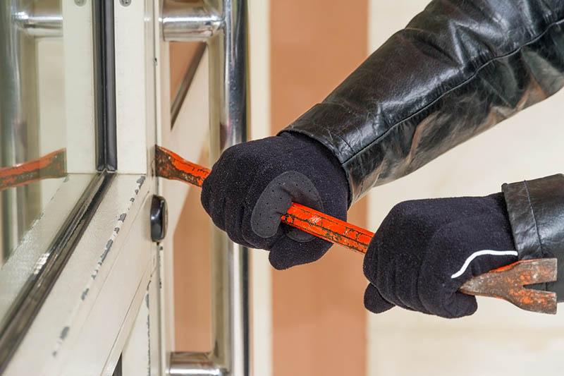 close-up of burglar's arms, using a crowbar to break open a door
