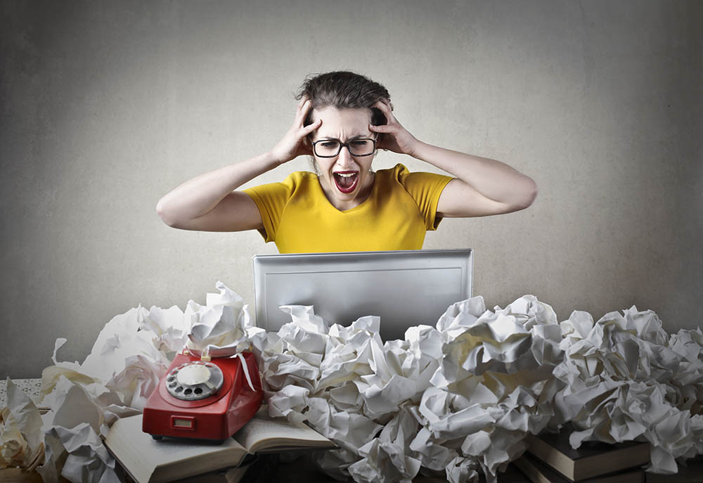 screaming lady behind laptop, surrounded by screwed up paper - free payroll software