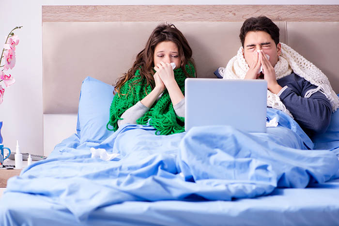 sick couple in bed with laptop - remote working and cyber security