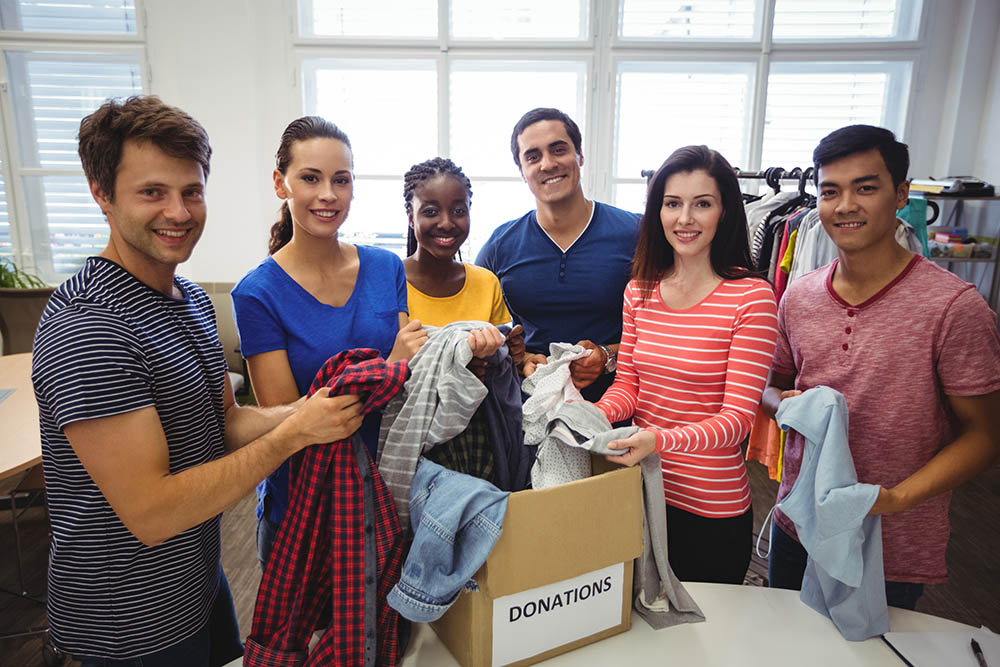 charity workers standing round a box of donated clothes - cybersecurity for charities