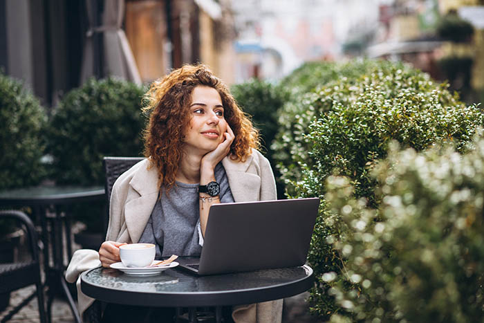 Lady sitting outside cafe with laptop and drinking coffee. She is looking off somewhere else instead of looking at her laptop WHERE HER WORK IS! - remote working and cybersecurity